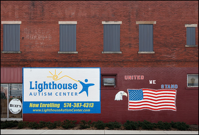 A patriotic mural with a large American flag and bald eagle on the side of a brick building on Main Street in Mishawaka, Indiana. The mural says United We Stand. An advertisement for Lighthouse Autism Center is painted on the wall next to the flag.