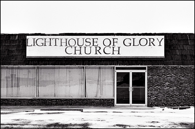 The Lighthouse of Glory church in an old storefront on State Road 930 in New Haven, Indiana on a snowy winter day.