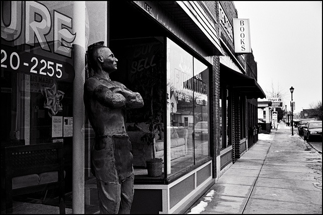 An old cigar store Indian standing on the sidewalk in front of Linda Lou's Furniture store on Wells Street in Fort Wayne, Indiana.