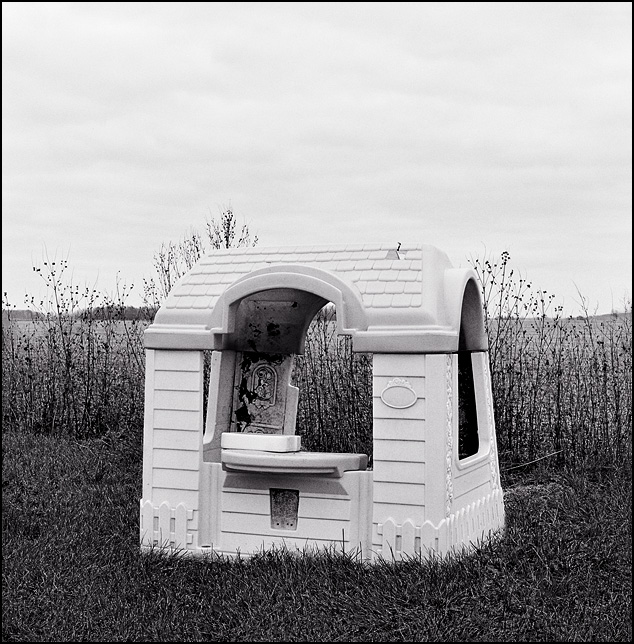 A Little Tykes plastic playhouse stands next to a field surrounded by tall weeds on an abandoned farm on Brindle Road in Allen County, Indiana.