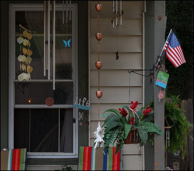 The porch on an old house decorated with several wind chimes, an American flag, and a sign that says Live Laugh Love.