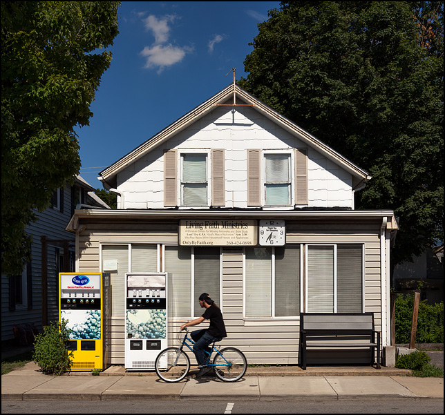 A man on a bicycle rides past Living Faith Ministries, a storefront church on Wells Street in Fort Wayne, Indiana. Two vending machines selling fruit juice stand in front of the church.