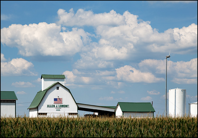 A modern steel barn with an American flag and a sign that says, Allen J. Lomont 1930. It stands behind a field of tall corn on the corner of US-30 and Girard Road in rural Allen County, Indiana.