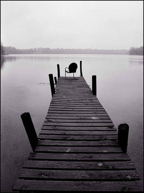 An antique metal motel chair on the end of an old weathered pier looking out over the water on a rainy day at Goose Lake in Whitley County, Indiana.