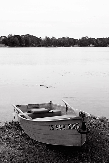 An aluminum rowboat with oars on the beach at Loon Lake in northeast Indiana.