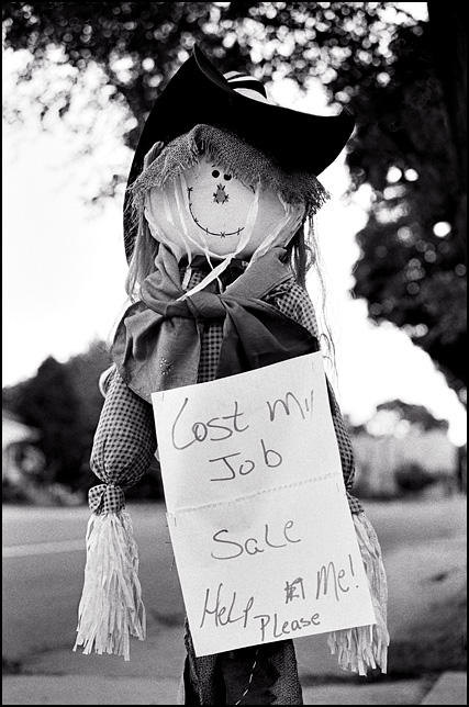 A scarecrow holding a sign that says Lost My Job, Yard Sale, Help Me Please! This was on Spy Run Avenue in Fort Wayne, Indiana.