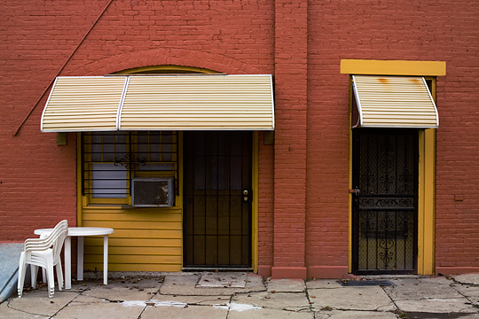 An old carriage house converted to apartments in Louisville, Kentucky. The brick building has been painted red and yellow, and modern doors and windows installed in the old entrances. A stack of plastic patio chairs sits in front of the house.