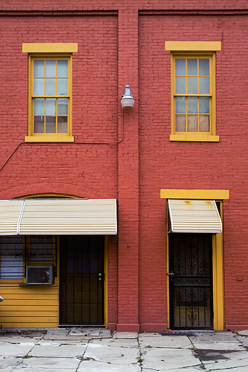 An old carriage house on Third Street in Louisville, Kentucky that has been converted to apartments. The brick building has been painted red and yellow and modern doors and windows installed in the old entrances.