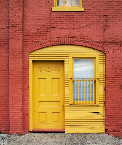 The door and window of an old carriage house on Third Street in Louisville, Kentucky that has been converted to apartments. The brick carriage house has been painted red and the windows and door are painted yellow. The first floor window is barred. The old wood panel door has a decorative relief on the top panel.