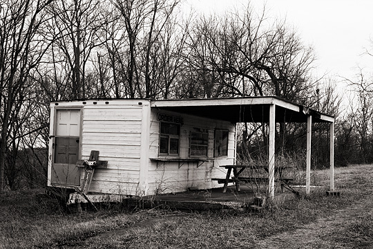 An abandoned hotdog stand on Louisville Road in rural Bullitt County, Kentucky with a memorial cross leaning against the end of the trailer.