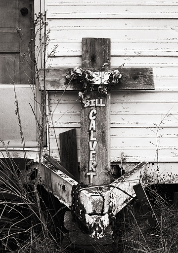 A wooden memorial cross decorated with silk flowers leaned against a trailer on Louisville Road in Bullitt County, Kentucky. The cross commemorates Bill Calvert, who was killed in an auto accident there.