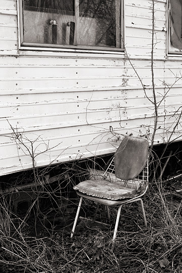 An old metal restaurant chair behind an abandoned hotdog stand in Bullitt County, Kentucky. The hotdog stand is a white trailer surrounded by trees and tall weeds.
