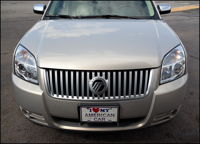 A 2008 Mercury Sable with a license plate on the front bumper that says, I love my American car.