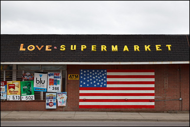 A giant American flag painted on the front of Love Supermarket on Union Street in Mishawaka, Indiana. The rest of the building is covered in signs advertising tobacco and junk food.