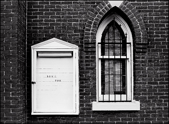 A sign that says I Love You next to a Gothic style window with iron bars on an old brick church on Muhammed Ali Road in Louisville, Kentucky.