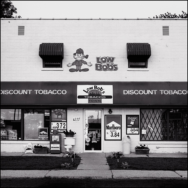 A Low Bob's Discount Tobacco Town store on Bluffton Road in the Waynedale area of Fort Wayne, Indiana. The windows are full of cigarette advertisements and signs for Camel, Marlboro, and Basic cigarettes. An old toilet sits on the sidewalk in front of the building next to a newspaper machine and a flower box.