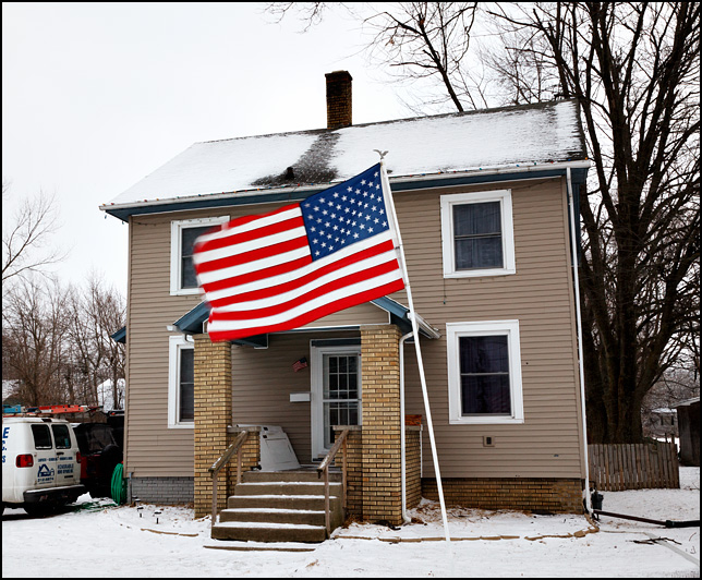 A large American flag flutters in the wind in front of a house on Lower Huntington Road in the Waynedale area of Fort Wayne, Indiana.