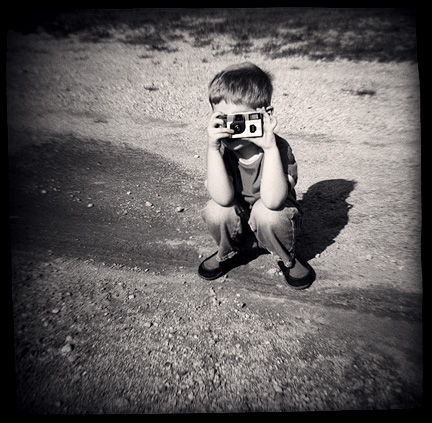 MacKenzie Crawford at age three taking pictures with a Fuji Quicksnap single-use camera. Photographed with a Diana toy camera.