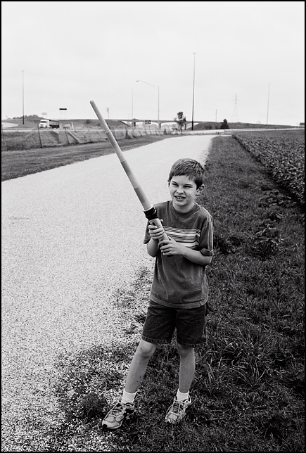 My son, MacKenzie Crawford, playing with his star wars lightsaber while I photograph along Interstate 69 in Indiana.