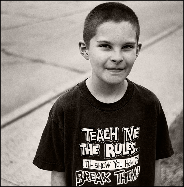 My son wearing a t-shirt that says, Teach me the rules and I'll show you how to break them.