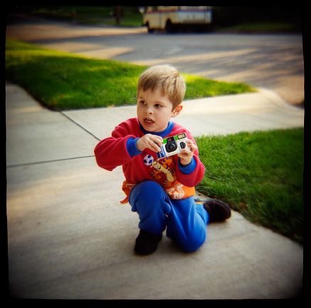 My three year old son winds the film on a single use camera. Photograph made with a Diana toy camera.