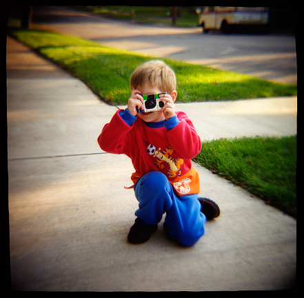 My son at age three taking pictures with a Fuji Quicksnap single use camera. Photograph made with a Diana toy camera.