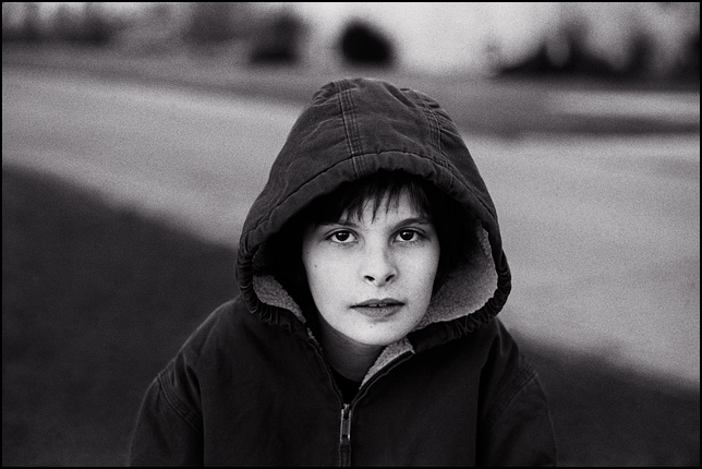 Portrait of my 11 year old son in a hooded jacket.
