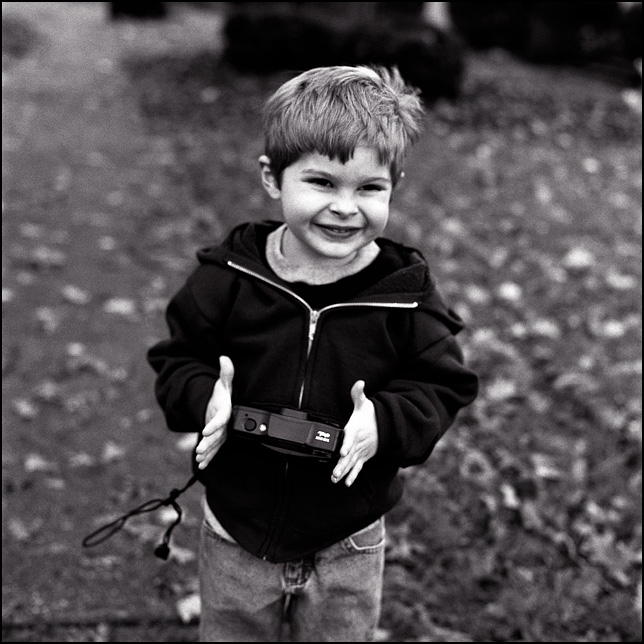 My son has a smile on his face as he lowers his camera after taking a photograph of me.