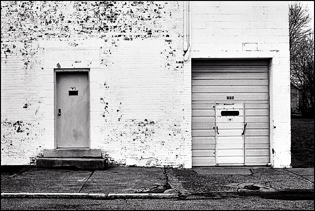 An abandoned whitewashed brick commercial building with garage door and a personnel door on Madison Street in Louisville, Kentucky.