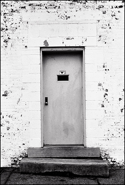 The crooked door of an abandoned brick commercial building on Madison Street in Louisville, Kentucky.