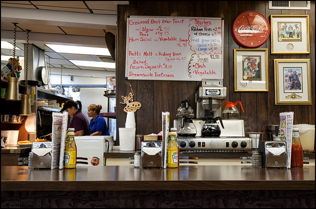 The lunch counter at the Magic Wand Restaurant in Churubusco, Indiana. Framed pictures of clowns cover the wall behind the counter with the kitchen and cooks visible beyond. Old fashioned napkin dispensers and glass ketchup bottles stand on the countertop.