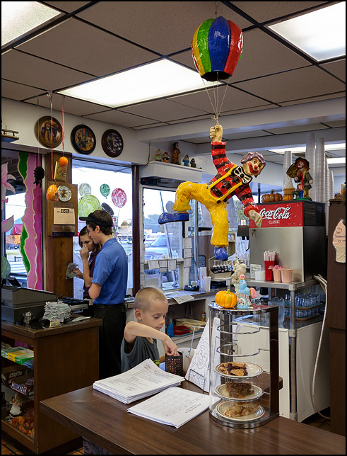 A little boy picks out crayons and coloring sheets on the counter of the Magic Wand Restaurant in Churubusco, Indiana. A clown with a balloon hangs above the counter and a dessert display full of pies stands under it.