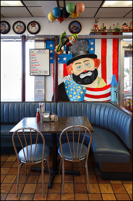 A clown wrapped in the American flag is painted on one of the front windows of the Magic Wand Restaurant in Churubusco, Indiana. A clown with balloons hangs from the ceiling and the walls are covered in paintings, plates, and figurines of clowns.