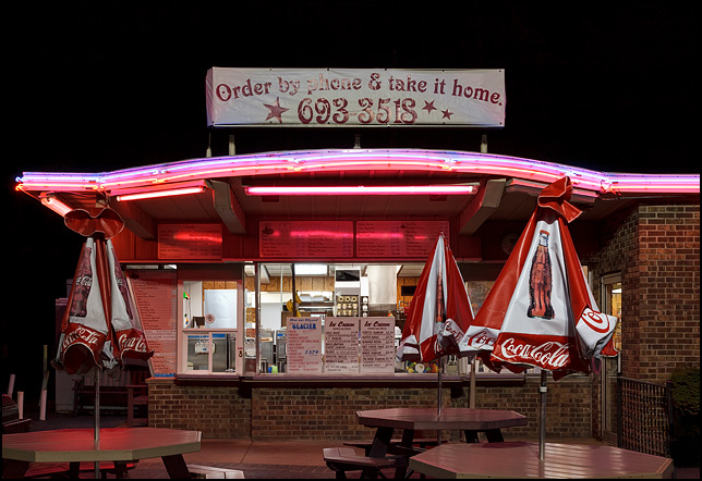The carry-out window at Magic Wand Restaurant in Churubusco, Indiana. Photographed at night with the neon lights turned on. Tables with Coca-Cola umbrellas provide seating in front of the restaurant.
