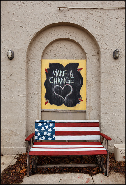 Make A Change, a sign written on a chalkboard with a big heart drawn on it. The sign hangs above a bench painted like the American flag in an alcove on the side of a stucco building on Broadway in Fort Wayne, Indiana. The building is a secondhand store called Little Shop of Lauras.