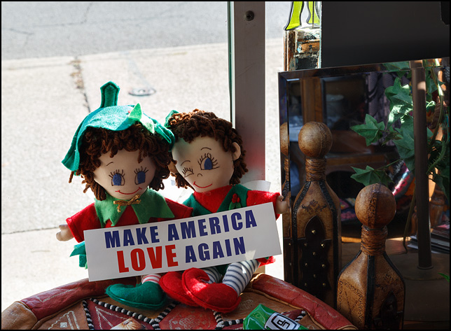 Two dolls holding a bumper sticker that says, Make America Love Again. They are sitting on a table in Little Shop of Lauras, a secondhand shop on Broadway in Fort Wayne, Indiana.