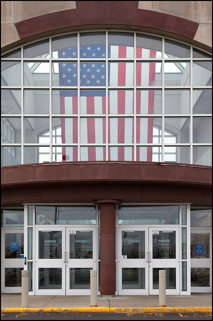 A very large American flag hanging in the glass paneled entryway of a shopping mall.