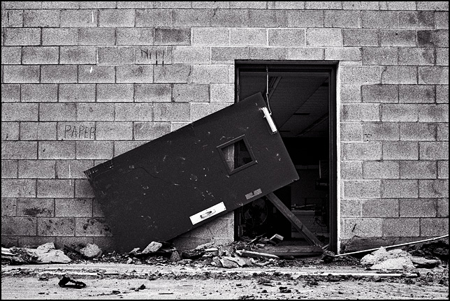 A steel door hangs lopsided from its broken hinges during the demolition of the former Maloley's store in Waynedale. The word Paper is written in chalk on the cinderblock wall next to the door.