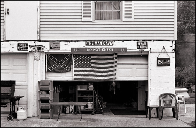 An American flag and a Confederate flag hang in a man cave in a garage in the small town of New Haven, Indiana. A basketball hoop hangs on the front of the building.