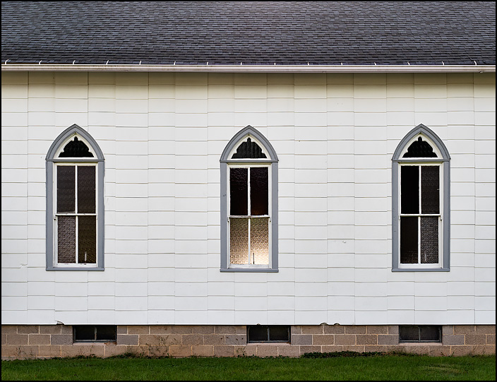 Pointed-arch windows on the side of Maples United Methodist Church, a small white wooden church in the small town of Maples, Indiana. The middle window glows with light.
