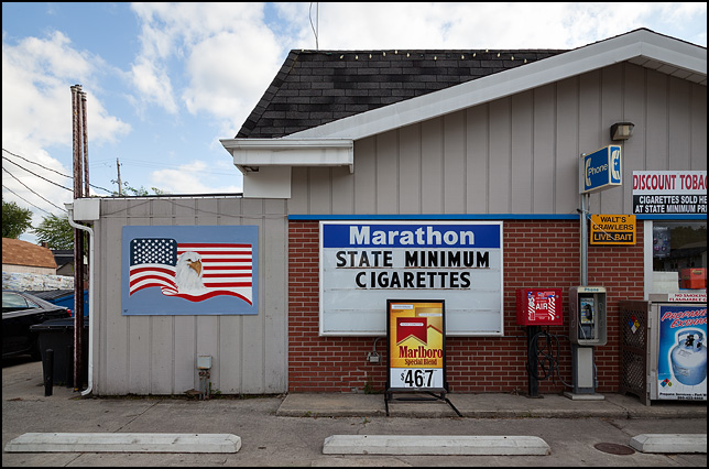 A sign advertising State Minimum Cigarette prices and a handpainted sign with an American flag and bald eagle on the front of a Marathon gas station in the small town of Warren, Indiana.