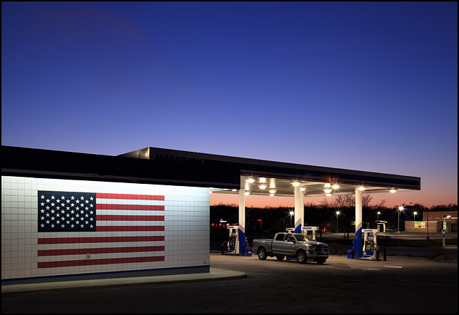 A large American flag painted on the side of a Marathon gas station on US-24 on the west side of Fort Wayne, Indiana. Photographed at sunset with a beautiful purple sky.