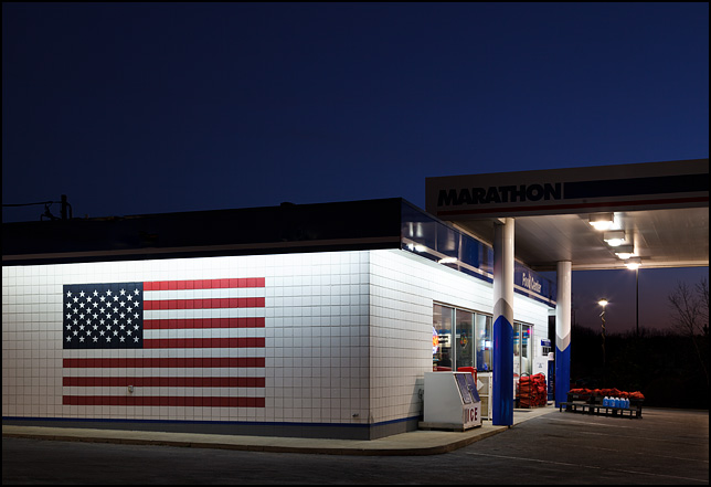 A huge American flag painted on the side of the convenience store at a gas station.