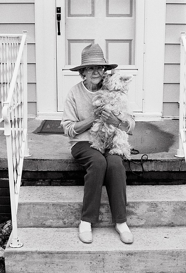 Marilyn Krick holds her Lhasa Apso while the little dog kisses the old woman's face.