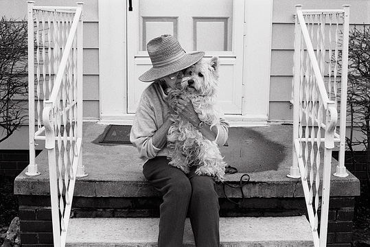 Marilyn Krick holds her Lhasa Apso dog on the front steps of her house.