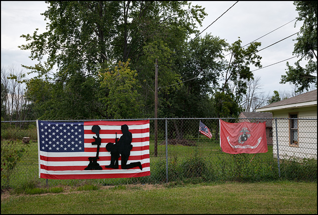 A fence with an American flag and a US Marine Corps flag hanging on it. A cut-out of a soldier kneeling in front of a battlefield cross hangs in front of the American flag.