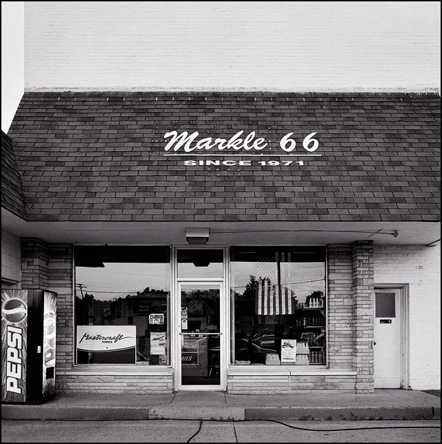 The Markle 66 Service Station in Markle, Indiana. An American flag hangs in the window an a Pepsi machine stands outside the door.