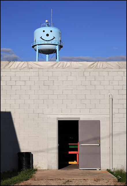 The water tower with the happy face stands above the ALH Building Systems factory in Markle, Indiana. One of the factory doors is open.