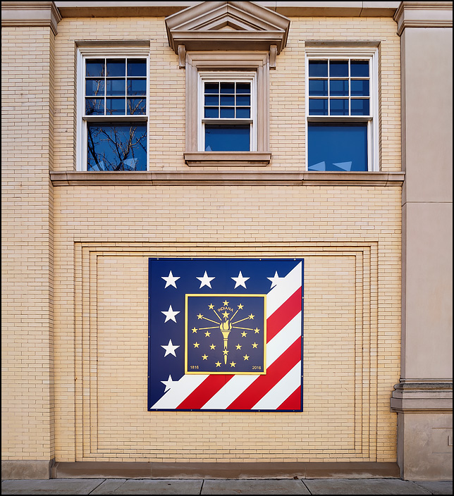 A mural of the American flag and the Indiana flag celebrating the Indiana statehood bicentennial on the side of the Marshall County Historical Museum in the small town of Plymouth, Indiana. The yellow brick neoclassical building is called the Lauer Building.
