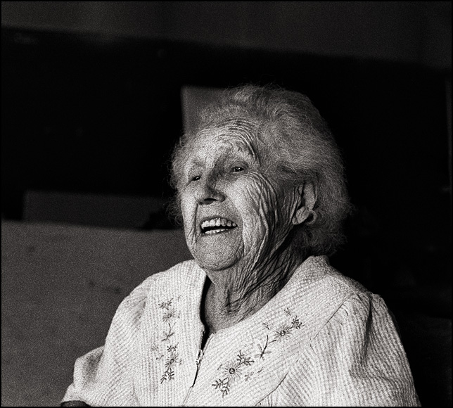 95 year old bar owner Mary Mora laughing while telling a story.
